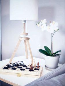 Schackbräde med pjäser på ett vitt bord med orkidée